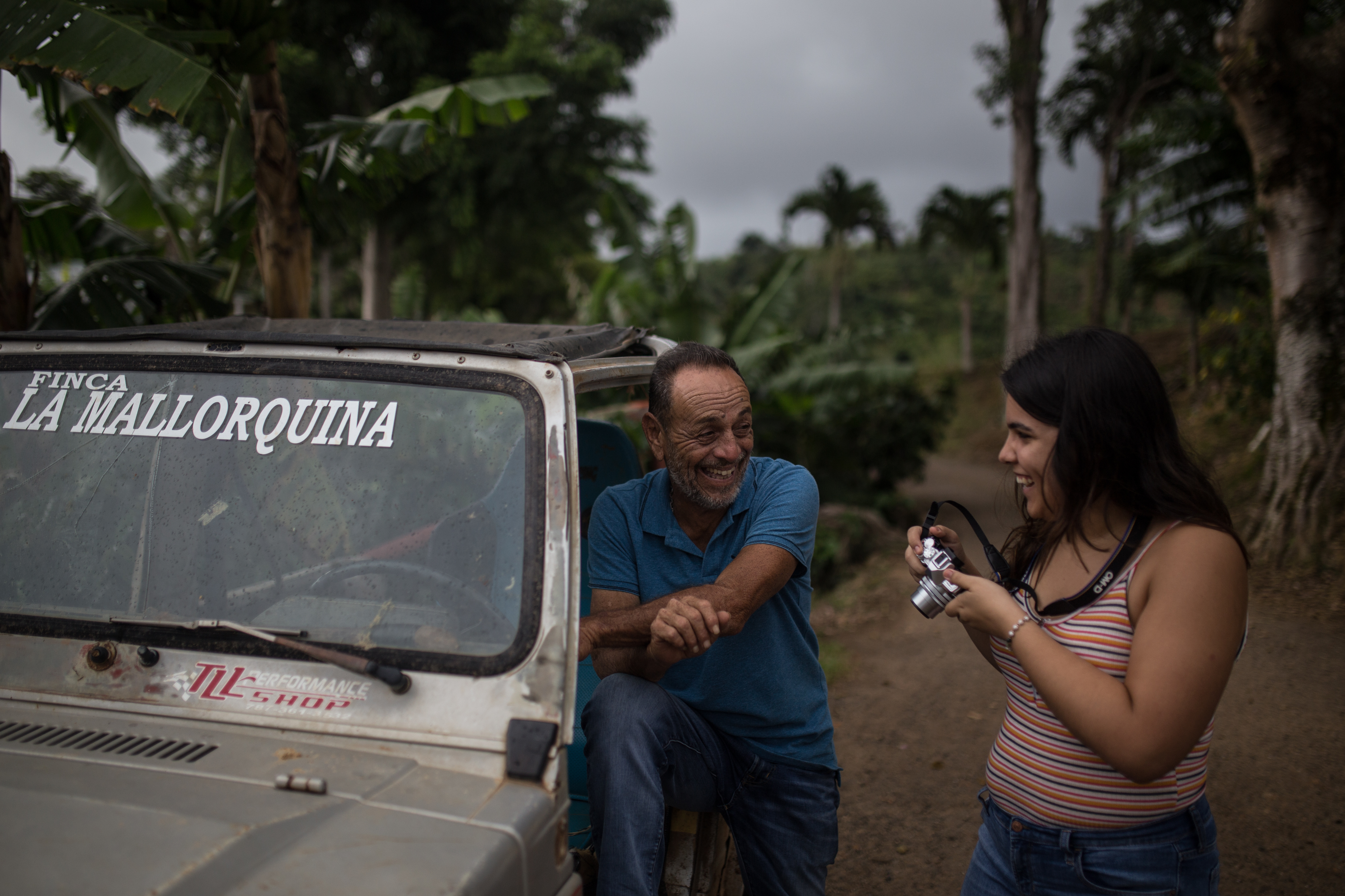 A young woman with a camera talks to a man who is standing beside a pickup truck.