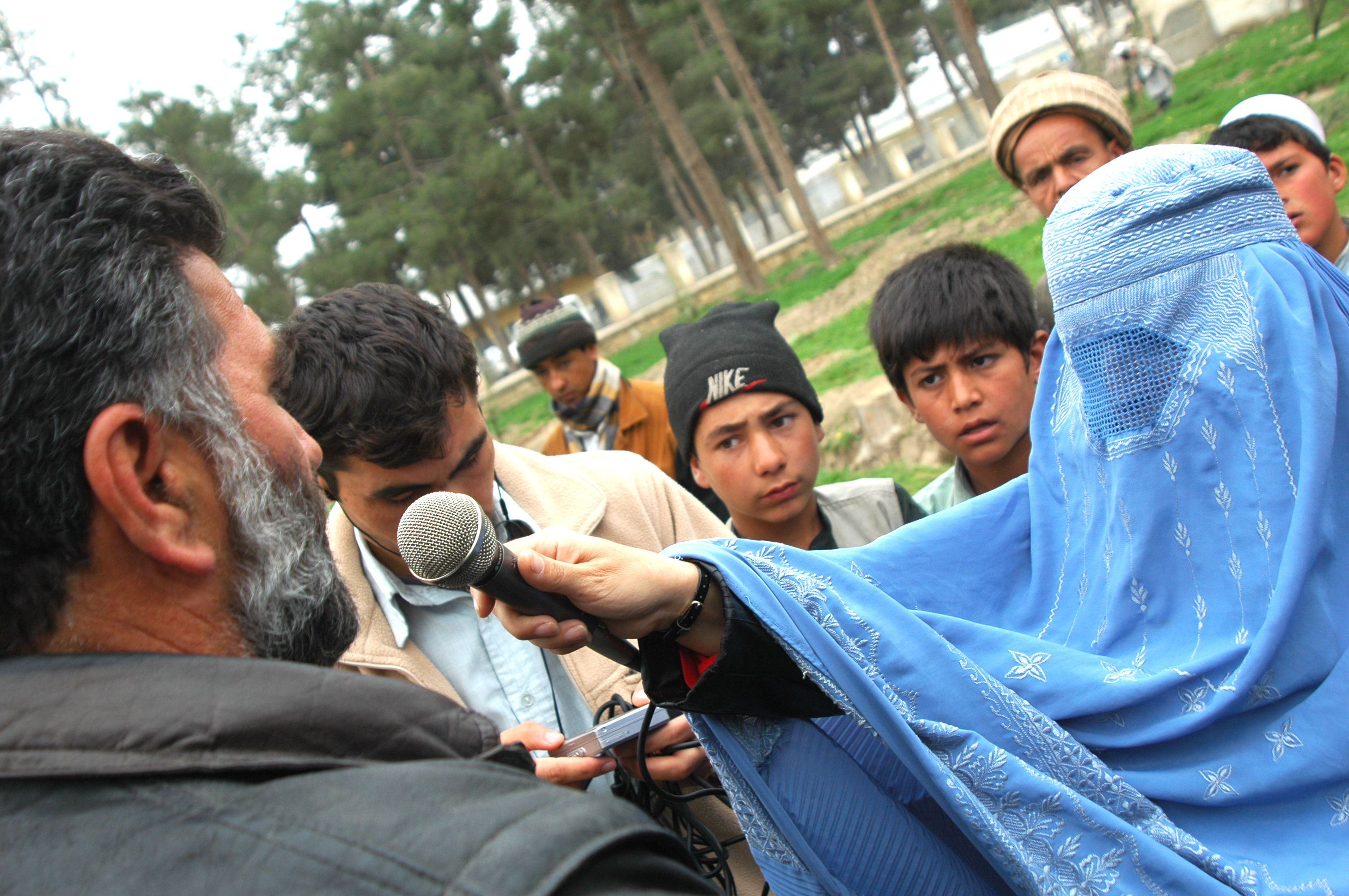 An Afghan woman in a burqa interviews some men