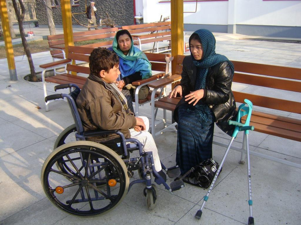Amina talks to a young man in a wheelchair while another woman looks on