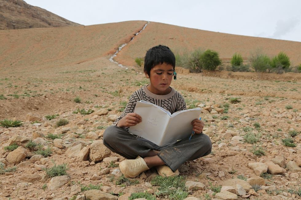 A young boy sits on the rocky ground, reading.