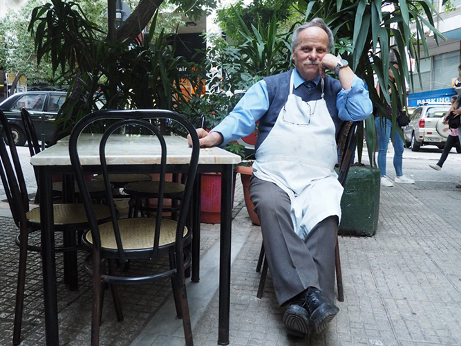 A man wearing a white apron sits at an outdoor table