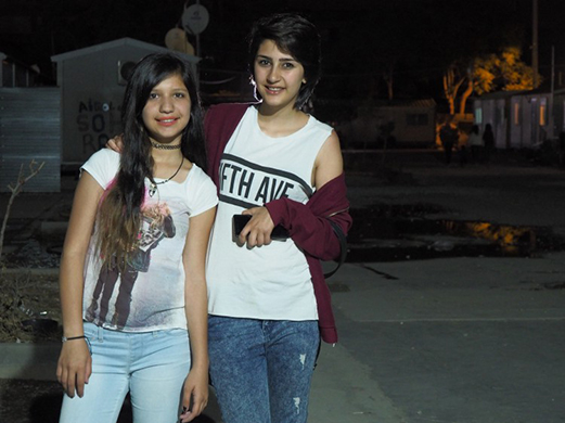 Two young women wearing t-shirts and jeans stand outside at night