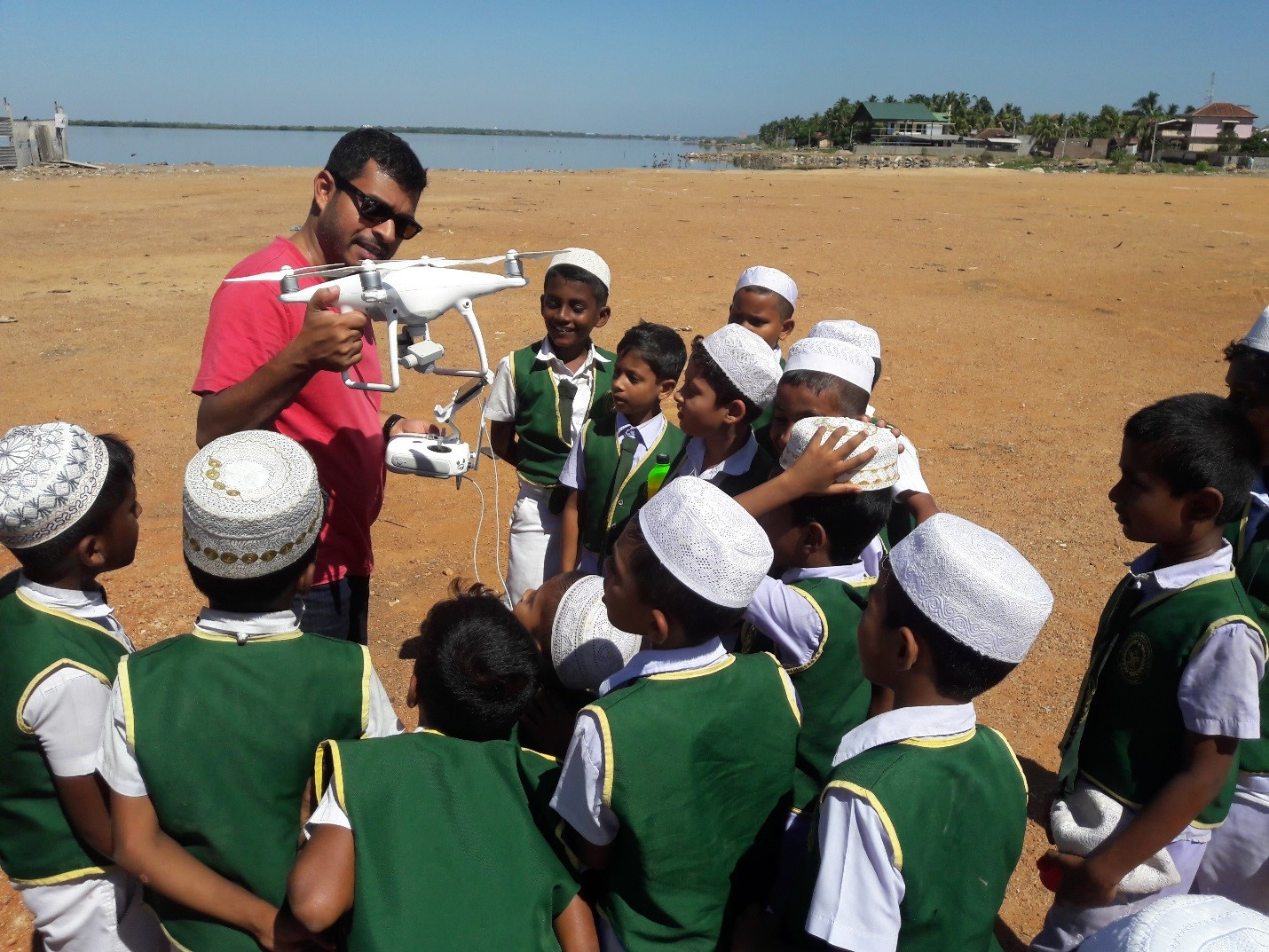 A man shows a group of school boys a drone