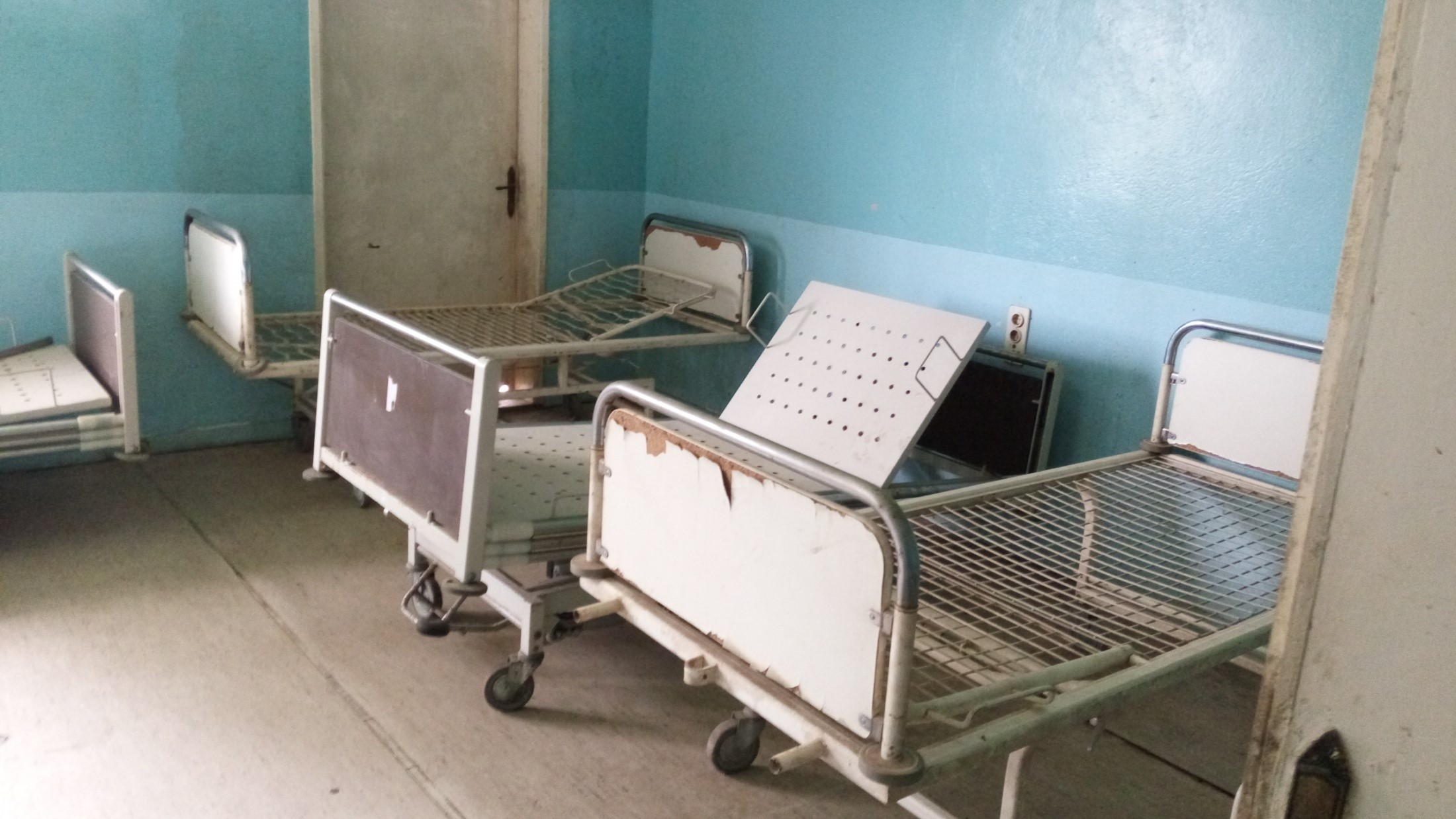 Empty metal beds in a hospital room.