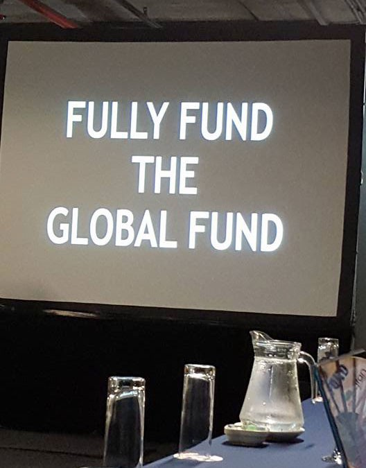 "A large sign says, ""Fully Fund the Global Fund"""