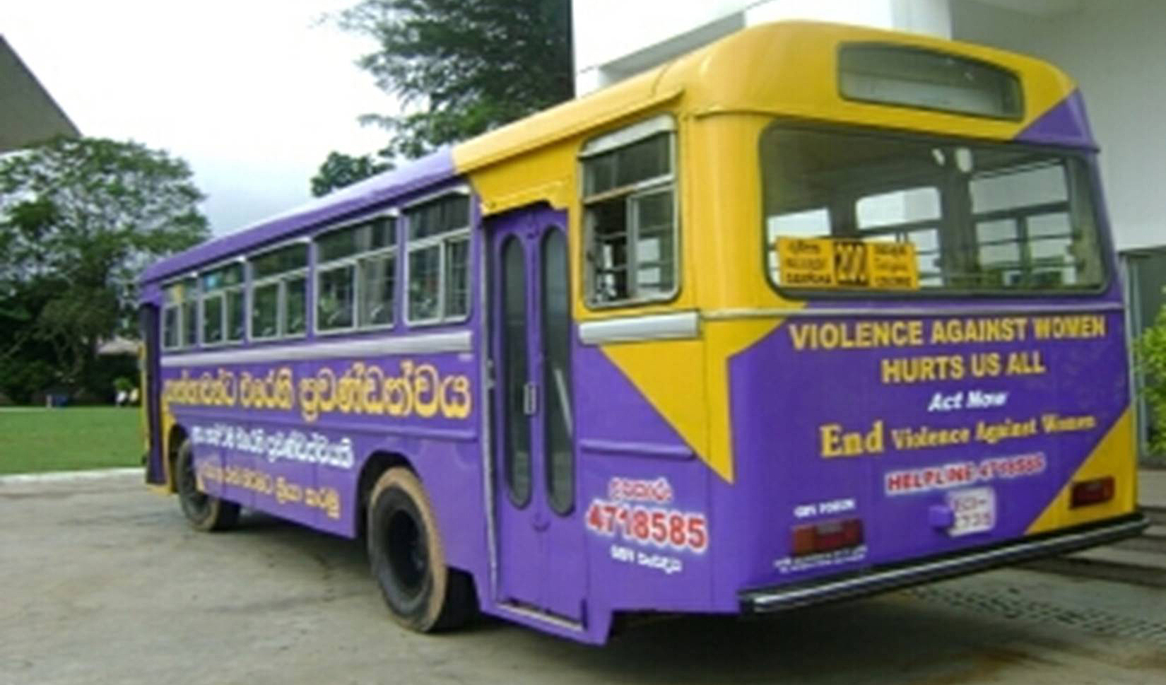 "A purple and yellow bus with ""Violence Aganist Women Hurts Us All"" written on it."