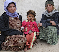 Two Iraqi women sit next to each other, one holds a child