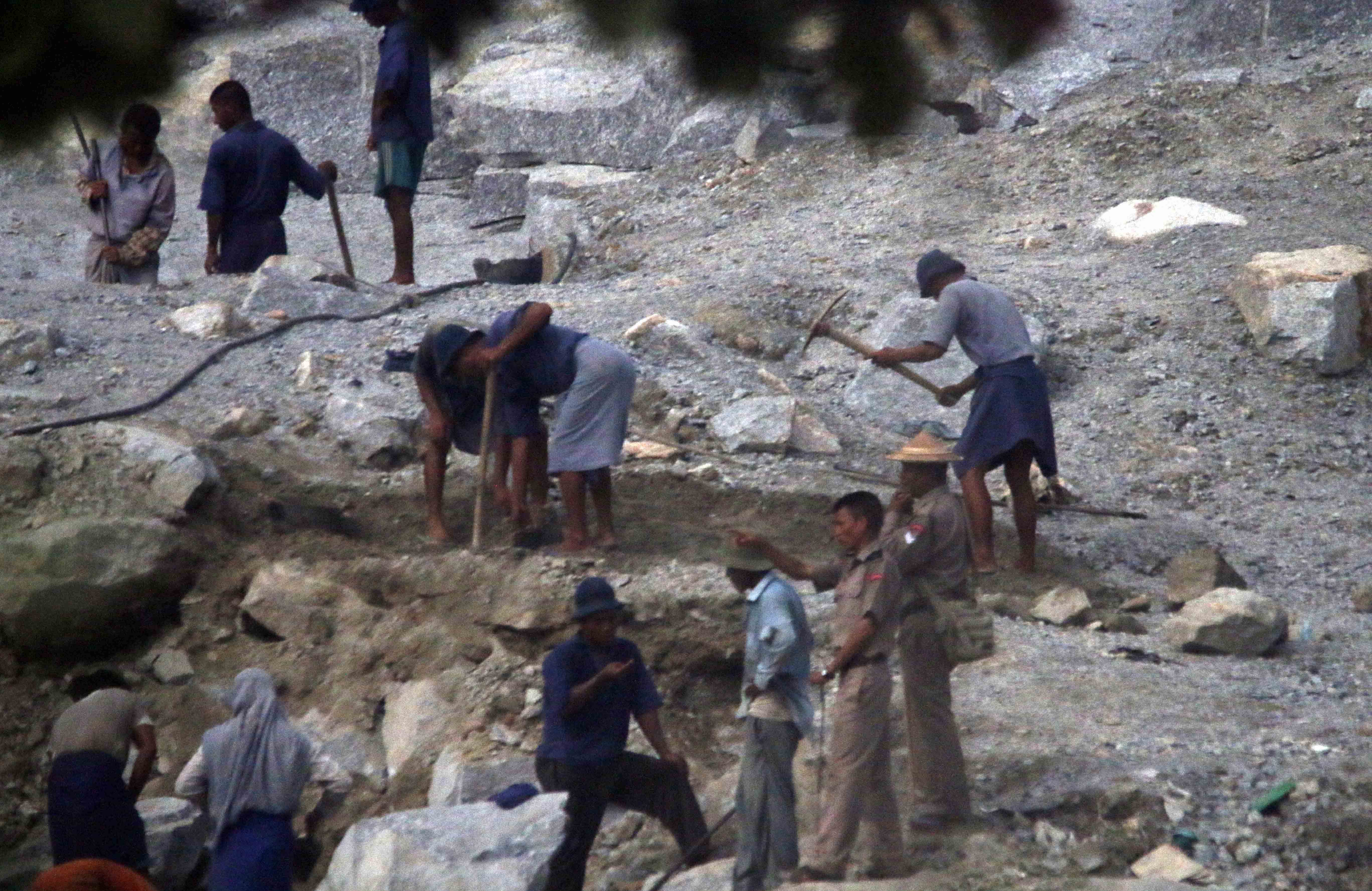 Prision laborers break rock in a quarry