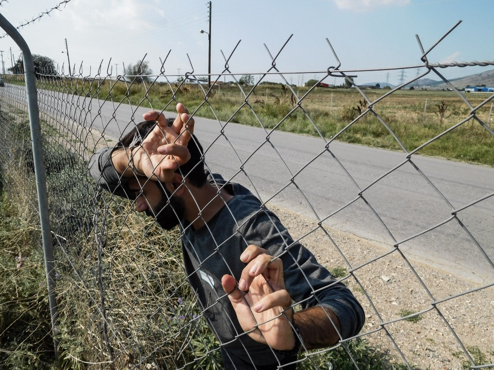 A man leans against a wire fence