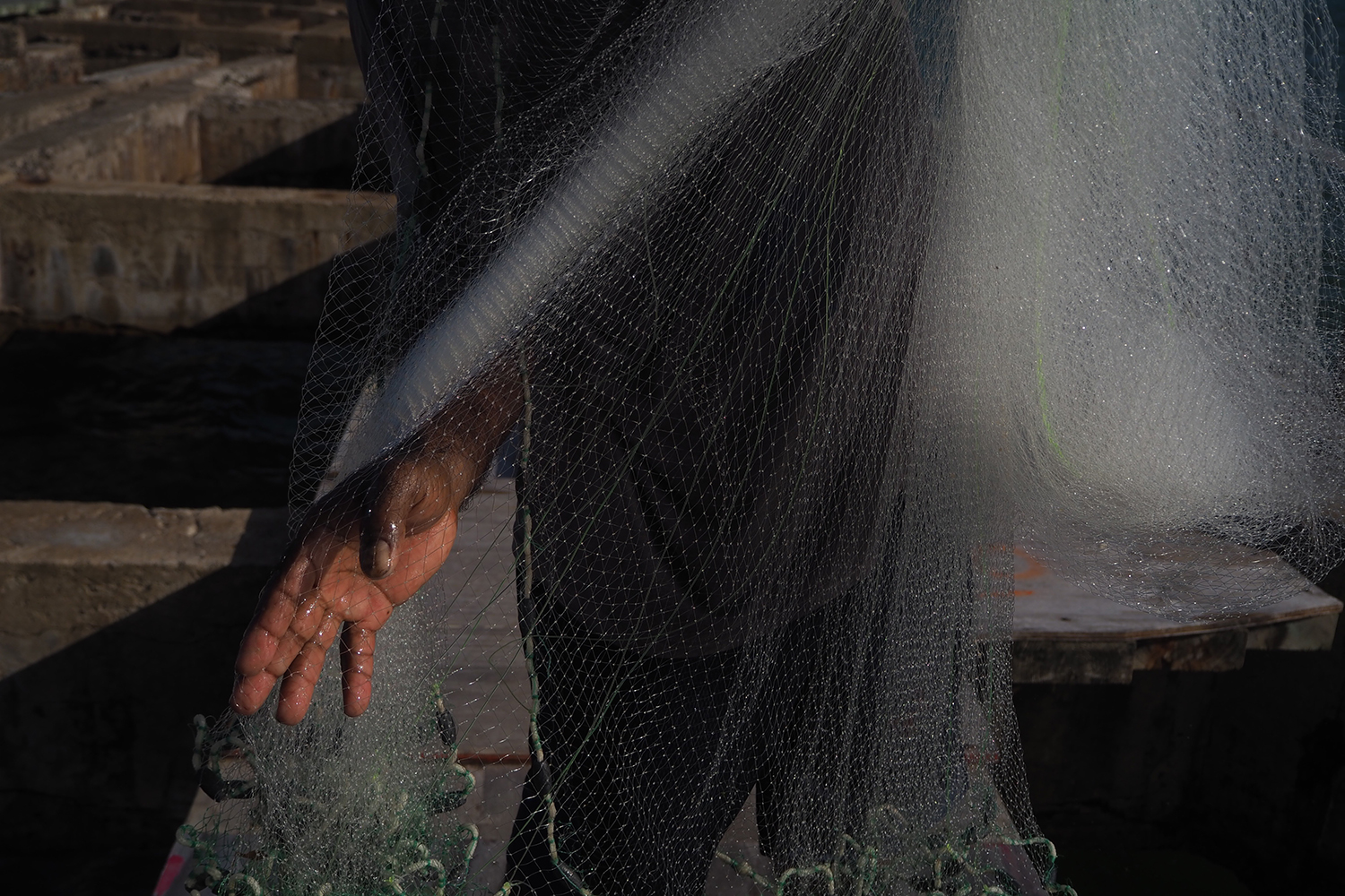 A hand holds a fishing net