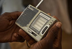 A portable radio being held in hands