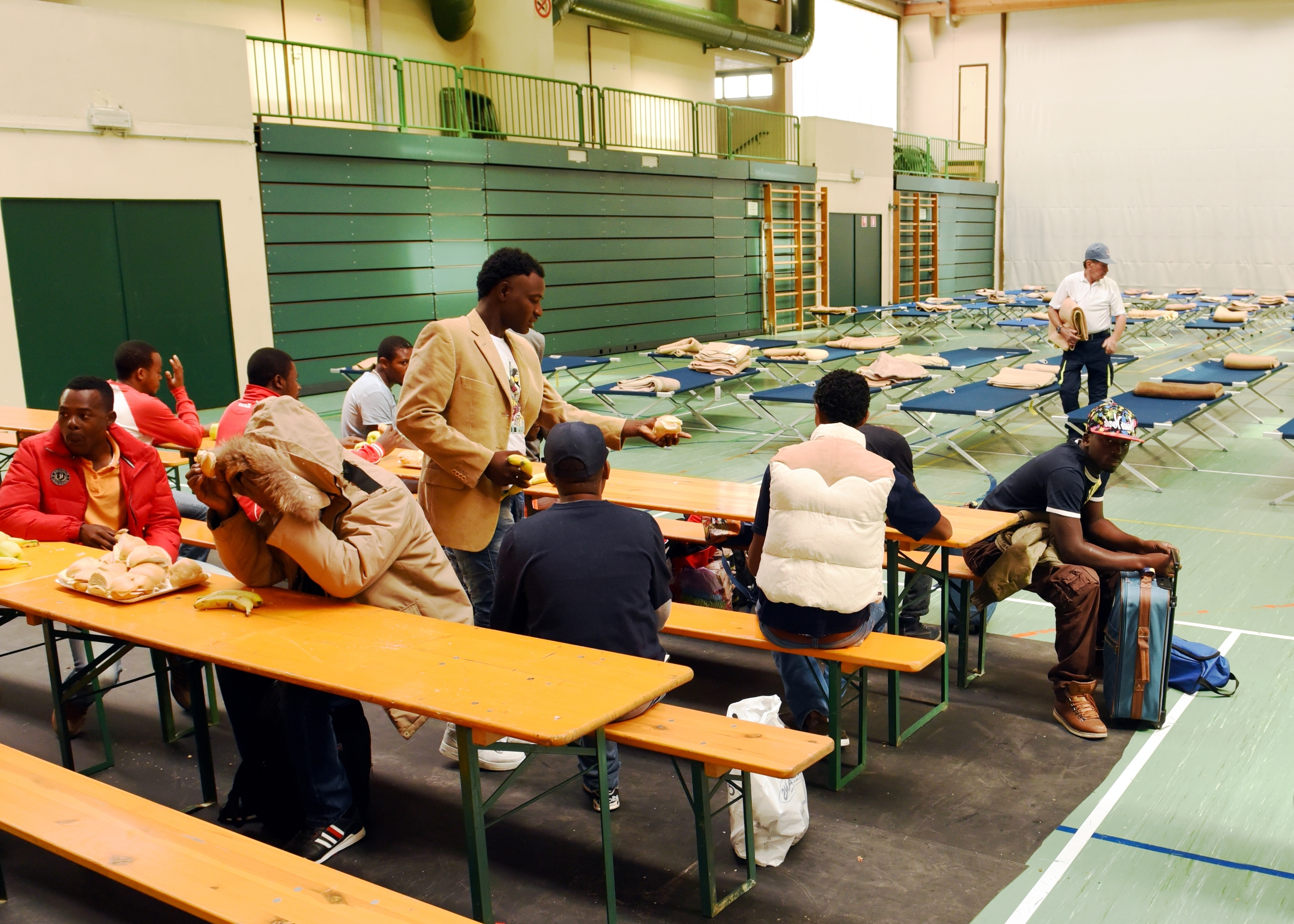 A group of men sit at tables inside a gym.