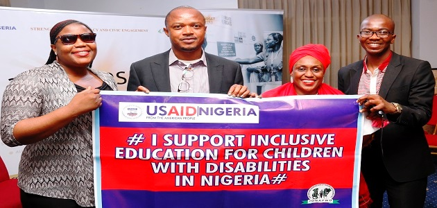 "Four people hold up a banner saying, ""I support inclusive education for children with disabilities in Nigeria."""