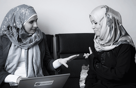 two women in headscarves talking with a laptop