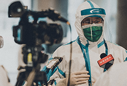 A person in full protective gear stands next to a video camera
