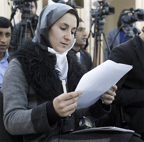 A woman journalists sits looking at a paper