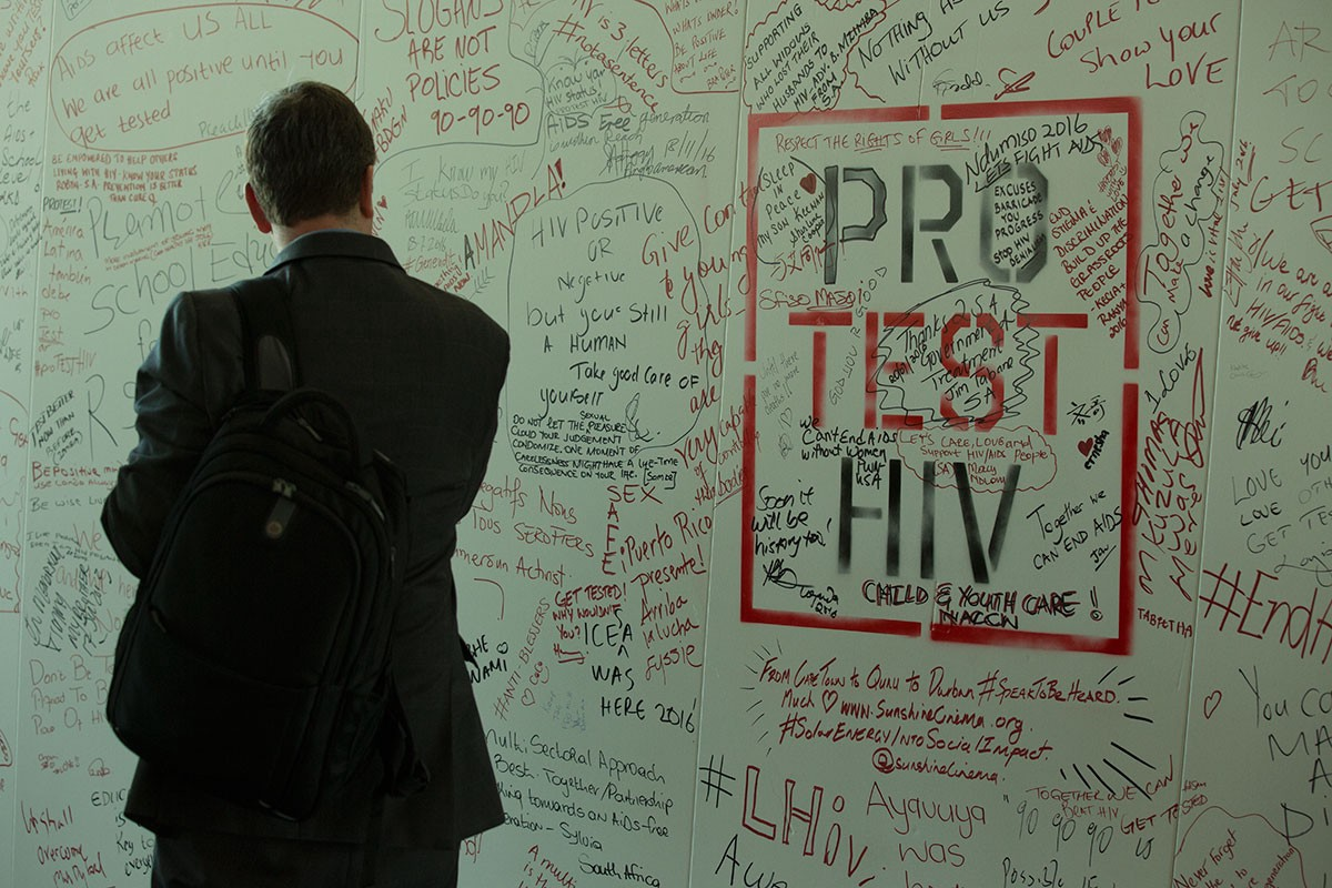 A man looks at a whiteboard with HIV messages on it