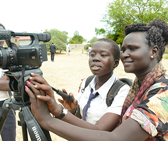 A woman demonstrates a video camera to a schoolgirl