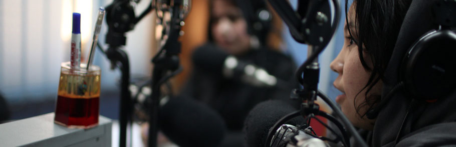 Woman journalist at a microphone in a radio studio
