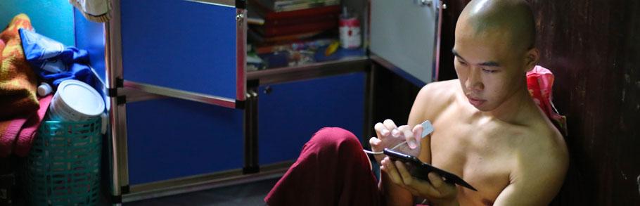 A Burmese monk uses his iPad