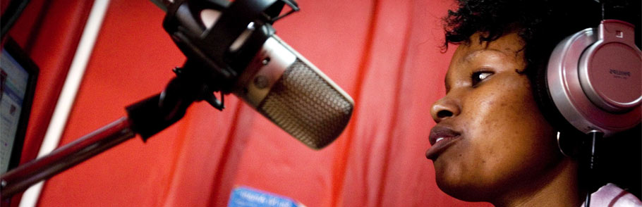 Kenyan reporter speaks into a mic at the radio studio