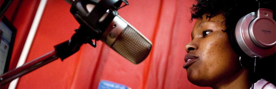 Kenyan reporter speaks into a mic at the radio studio