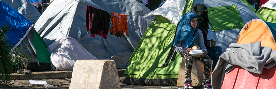 A young girl sits outside a tent in a refugee camp