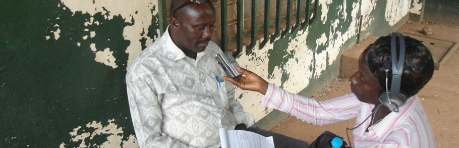 A female reporter interviews a man outside a building