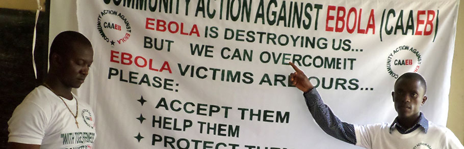 Two men stand in front of a banner about Ebola