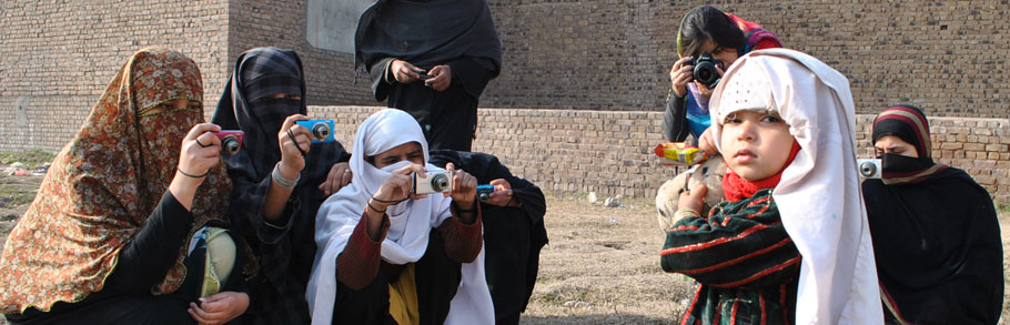 Women journalists photograph a young girl