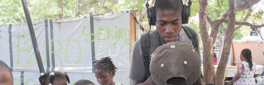 A Haitian reporter interviews some children in the street