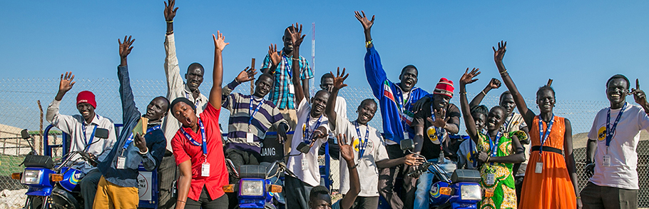 Group of journalists from South Sudan smile and wave.