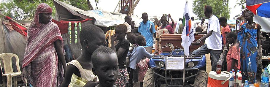People in a IDP camp in South Sudan gather around the Boda Boda Talk Talk vehicle