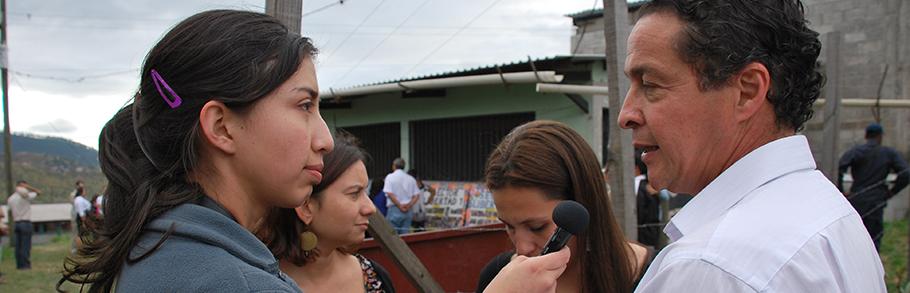 A woman reporter interviews a man outside