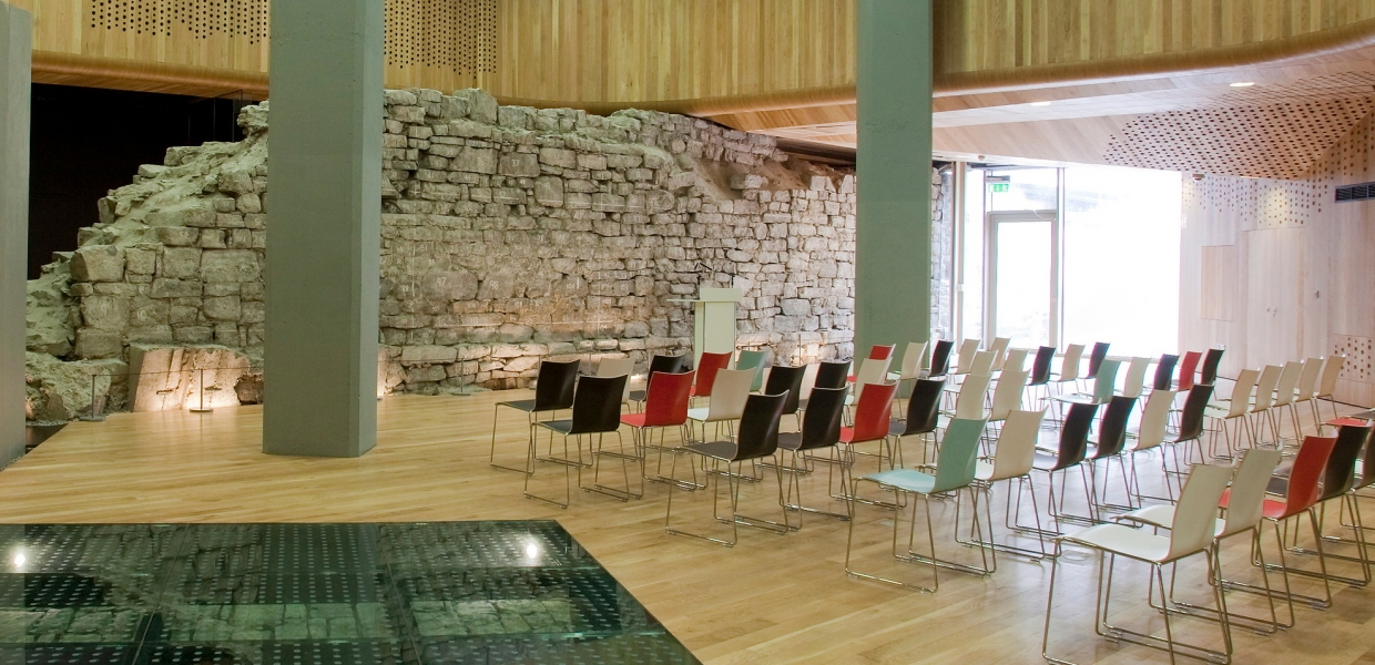 Rows of chairs in a light airy room with stone walls