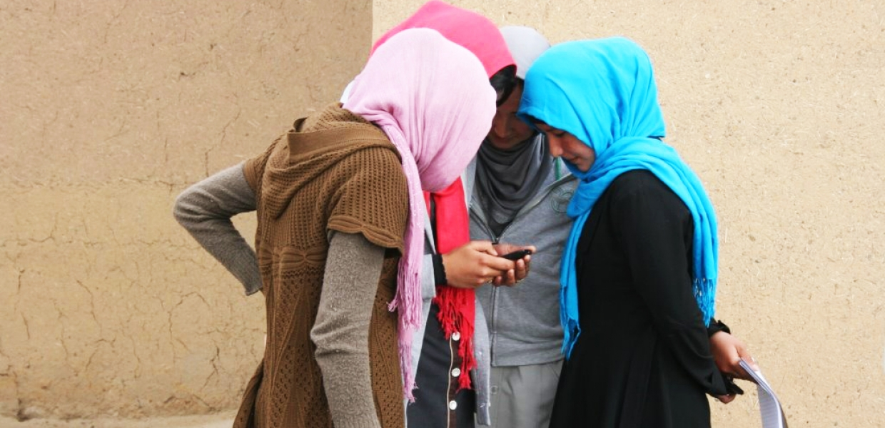 Four young women in headscarves look at a mobile phone