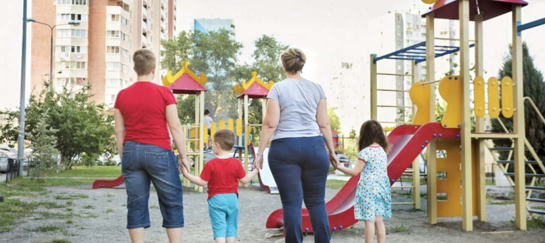 In a playground, two women stand holding the hands of a little boy and a little girl. Their backs are to the camera.