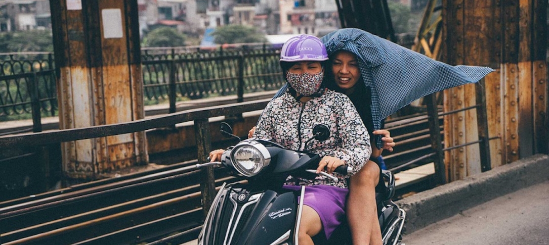 Two women ride a motor scooter over a bridge in Vietnam, one wears a face mask.