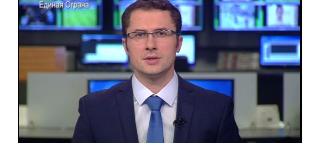 Screenshot from a tv broadcast - a man sits looking at the camera
