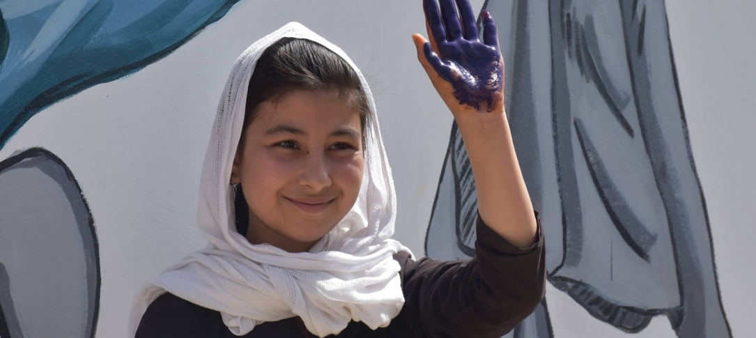 A girl holds up her hand - the palm is painted purple.