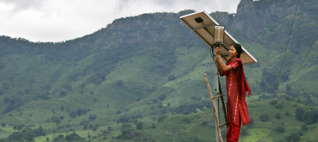 A woman climbs on a tall structure that has a solar panel on it.