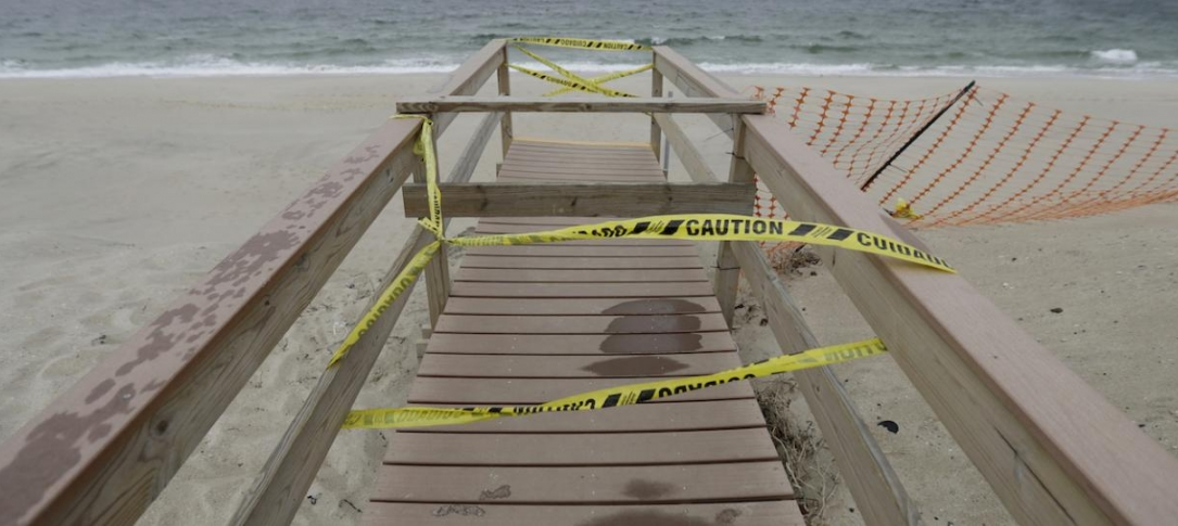 A boardwalk out to a beach has caution tape on it