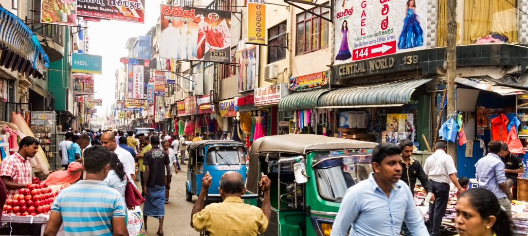 People and small vehicles on a Sri Lankan street.