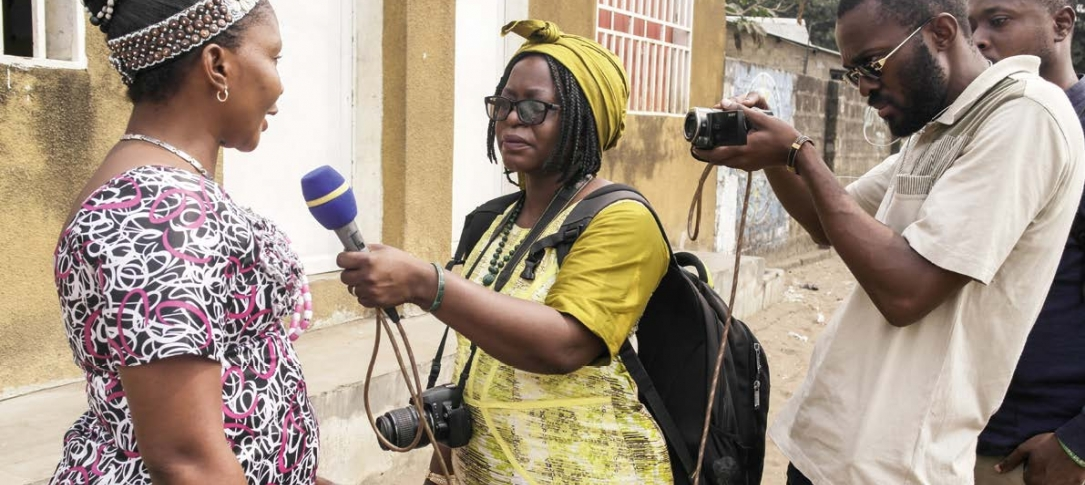 A woman journalist interviews a woman while a man videotapes.