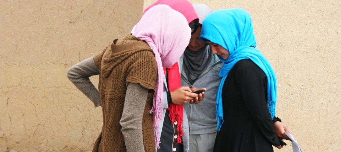 Four young Afghan women look at a cell phone in one of the girl's hands.