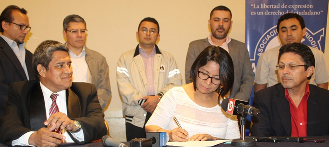 A woman signs a document sitting at a table. Five men stand behind her and two men sit next to her.