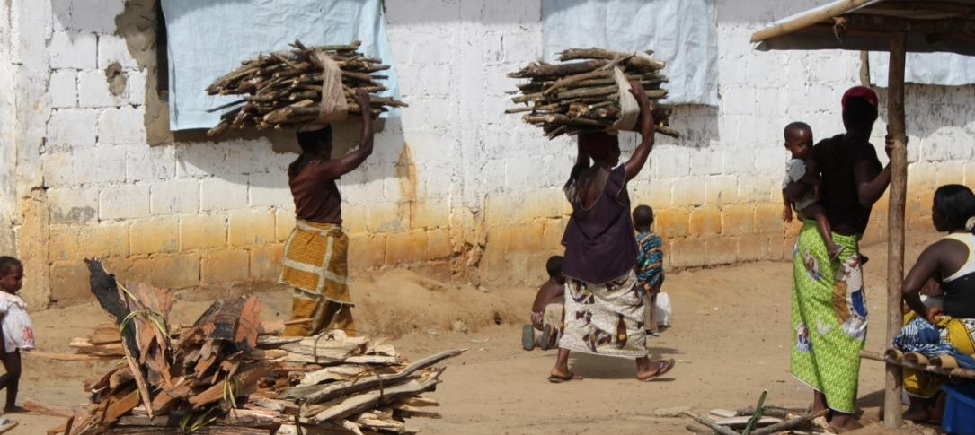 Street scene - women carrying bundles of sticks on their heads walk by a brick wall
