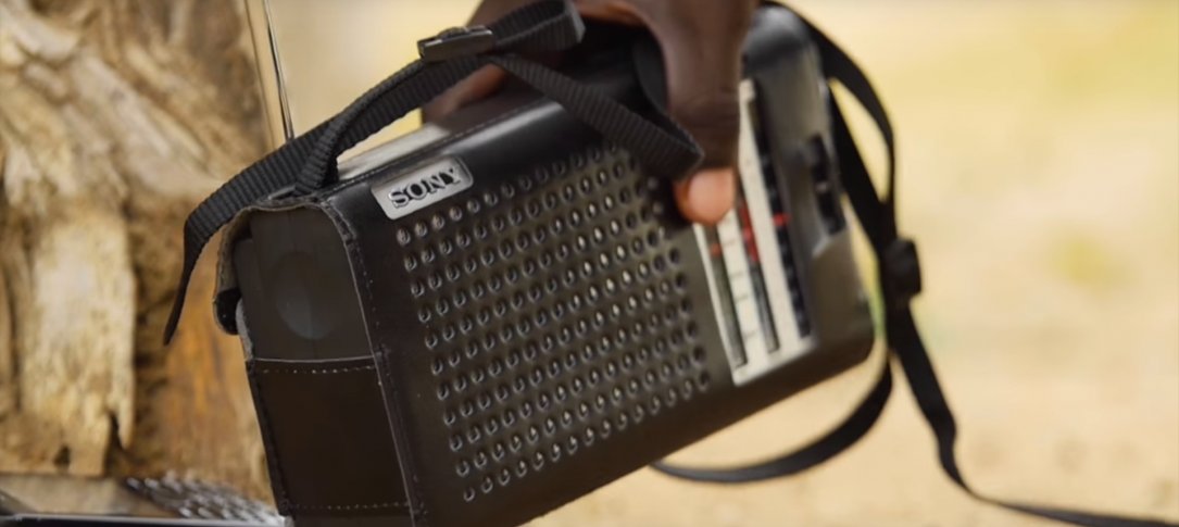 A portable radio is held in someone's hand