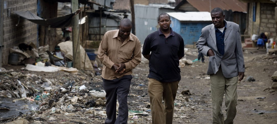 Three men walk through an area of rubble and trash