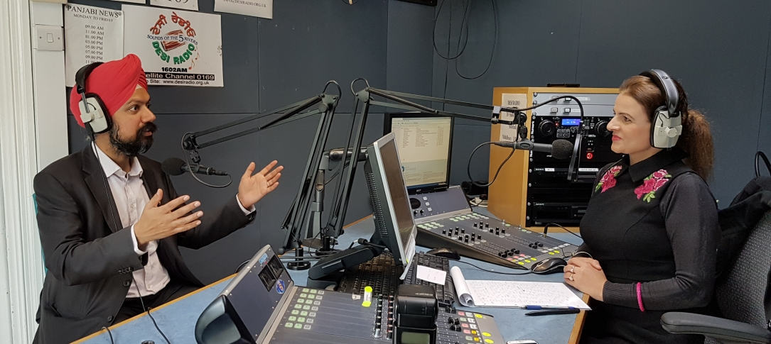 In a radio studio, a man wearing a red turban and a suit sits across a table from a woman wearing headphones.